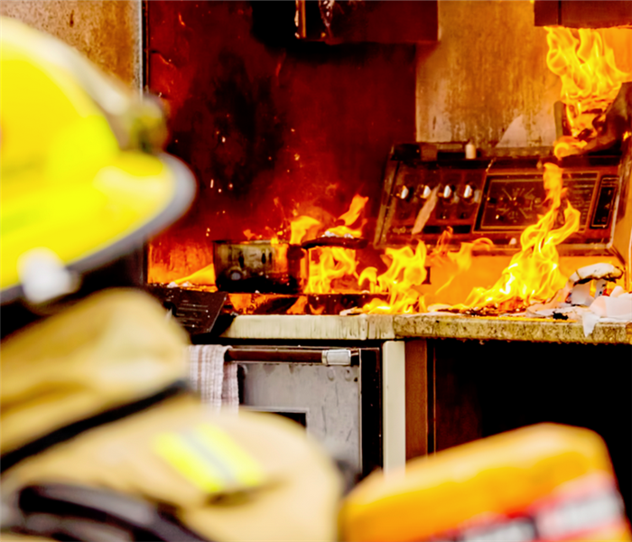 a kitchen stove on fire which has spread to the rest of the kitchen