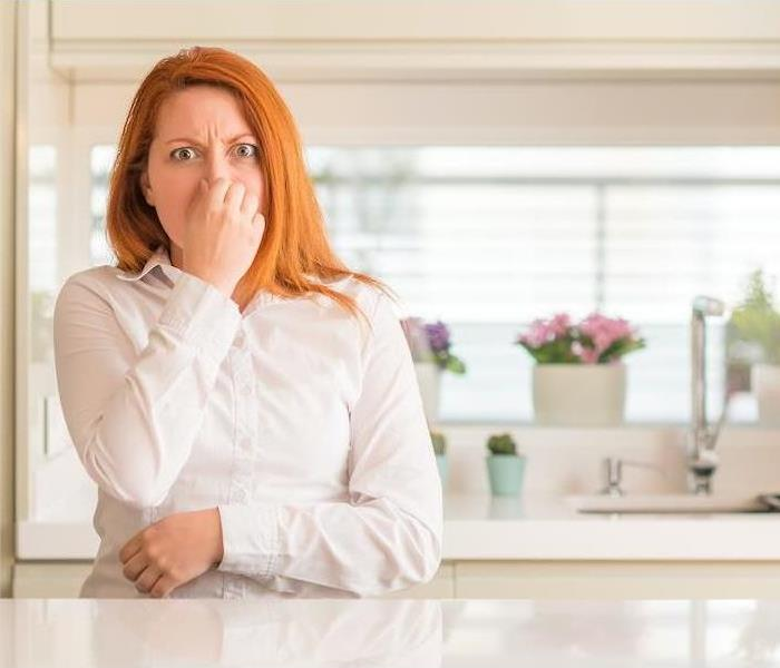 Redhead woman at kitchen smelling something stinky, holding breath with fingers on nose