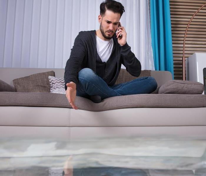 A man sitting on a couch with standing water in the home.