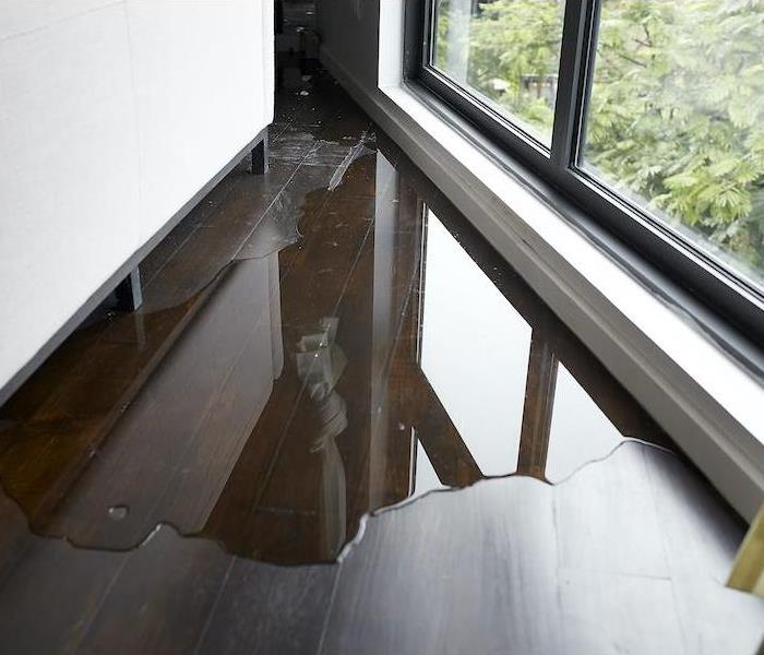 Water leaking and flooded on hardwood floor next to a window
